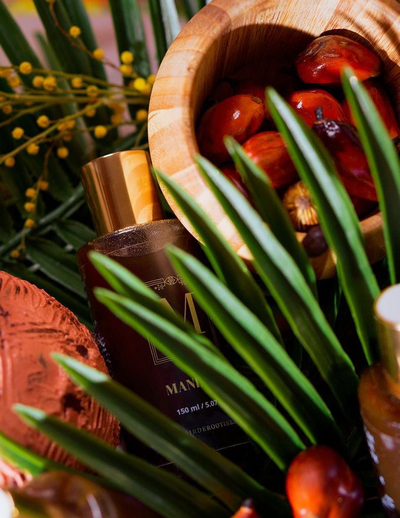 Flacon de Maningou dans un décor fait de branches de palmier et de noix de palme